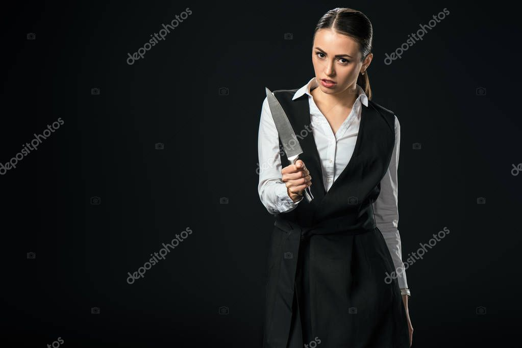 young beautiful businesswoman holding knife, isolated on black