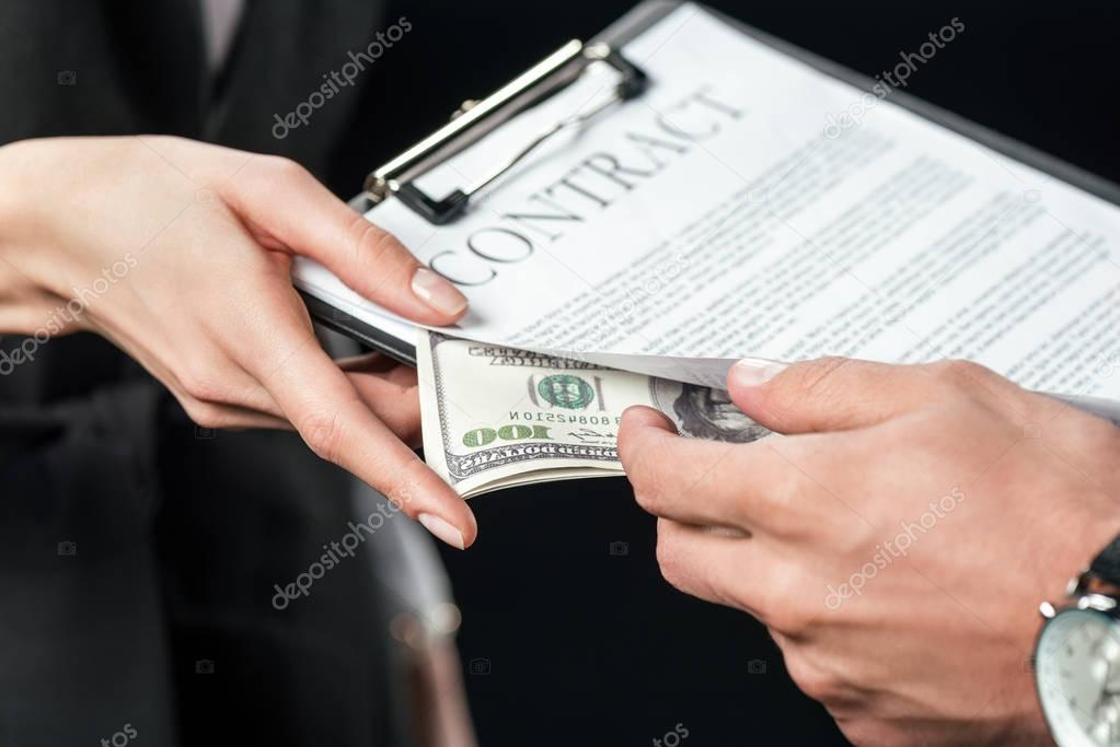 cropped view of businesspeople holding contract and bribe, isolated on black