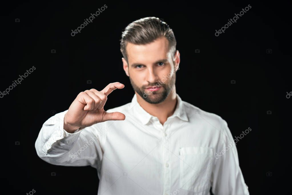 selective focus of handsome businessman showing size, isolated on black