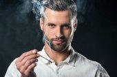 Fotografie gut aussehend Kaufmann Holding Match mit Rauch, isoliert auf schwarz