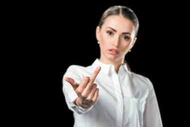 selective focus of woman showing middle finger, isolated on black