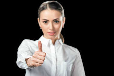 selective focus of businesswoman showing thumb up, isolated on black
