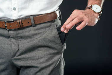 cropped view of poor businessman with empty pocket, isolated on black