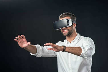 Smiling man using virtual reality headset, isolated on black stock vector