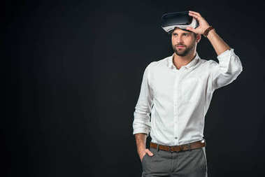 handsome man using virtual reality headset, isolated on black