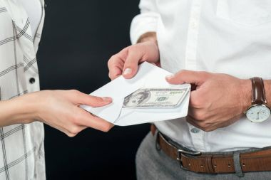 cropped view of businesspeople holding envelope with money, isolated on black