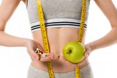 cropped shot of slim woman holding fresh apple and pills isolated on white