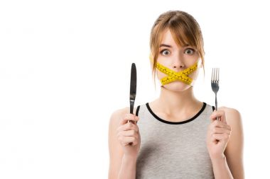 shocked young woman with measuring tape tied around her mouth holding fork and knife isolated on white
