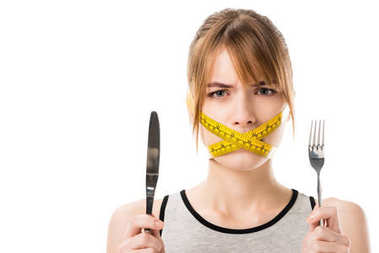 Young woman with measuring tape tied around her mouth holding fork and knife isolated on white stock vector