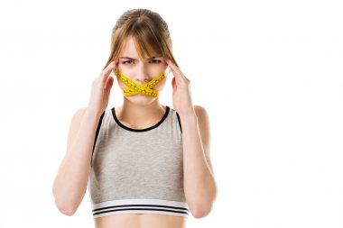 young woman with measuring tape tied around her mouth having headache isolated on white