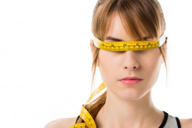 Close-up portrait of young woman with measuring tape tied around her eyes isolated on white stock vector