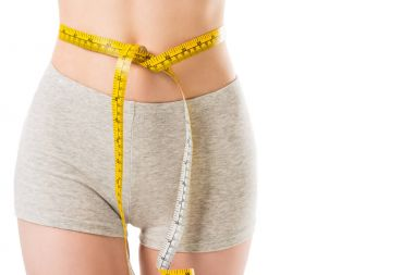 cropped shot of slim woman with measuring tape tied around her waist isolated on white