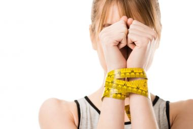 woman covering face with hands tied in measuring tape isolated on white
