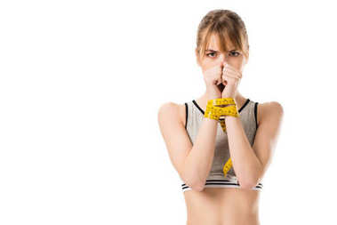 slim woman covering face with hands tied in measuring tape isolated on white