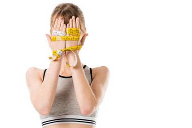 young woman covering face with hands tied in measuring tape isolated on white
