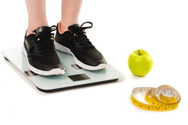 cropped shot of woman standing on scales with apple and measuring tape lying on floor isolated on white