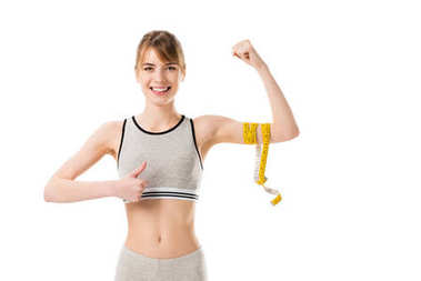 young slim woman showing her biceps tied with measuring tape and thumb up isolated on white