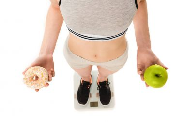 cropped shot of slim woman with apple and doughnut standing on scales isolated on white