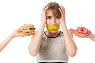 young woman with mouth tied in measuring tape screaming while people giving her junk food isolated on white