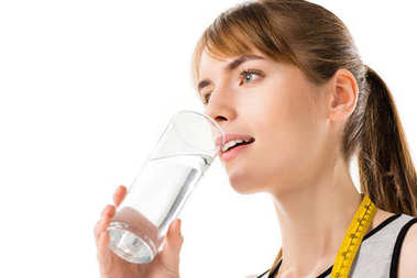 young woman with measuring tape on neck drinking water isolated on white