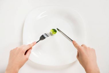 cropped shot of woman eating small piece of broccoli with fork and knife