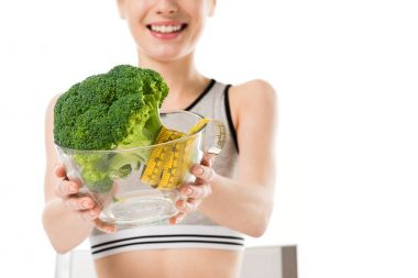 cropped shot of slim woman with broccoli covered in measuring tape in bowl isolated on white