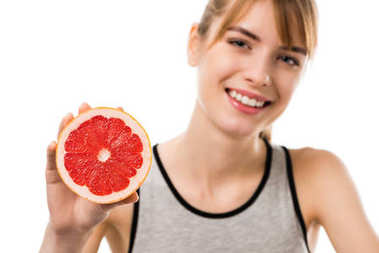 young happy woman with half of grapefruit isolated on white
