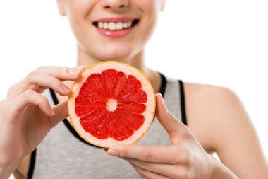 cropped shot of young smiling woman with half of grapefruit isolated on white