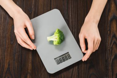cropped shot of woman measuring weight of broccoli