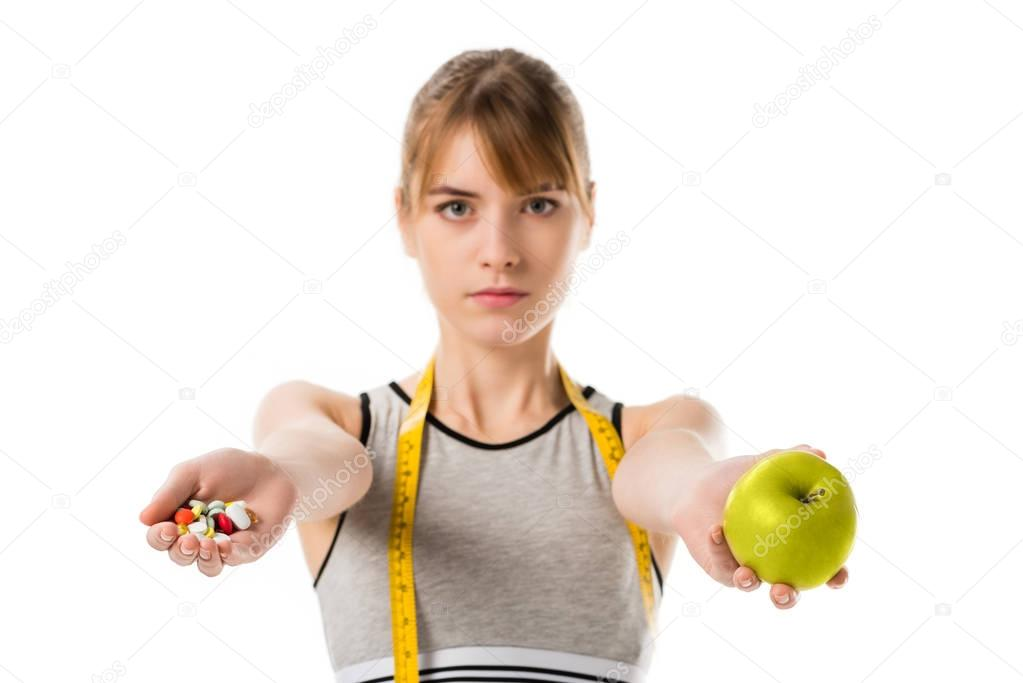 young slim woman holding fresh apple and pills isolated on white