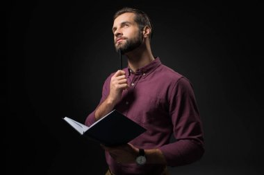 portrait of pensive businessman with notebook isolated on black