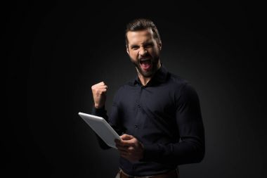 portrait of excited man with digital tablet isolated on black