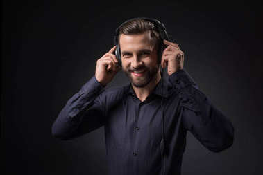 portrait of smiling man listening music in headphones isolated on black