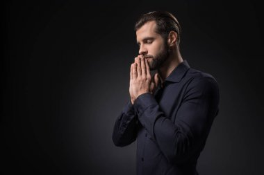 side view of man praying isolated on black