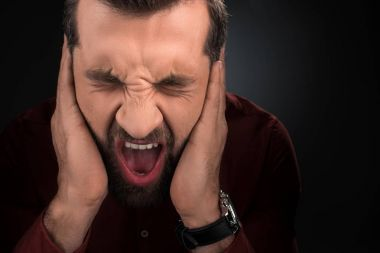 portrait of screaming man covering ears isolated on black