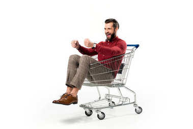 cheerful man sitting in shopping cart isolated on white
