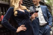 Photo cropped shot of beautiful adult couple drinking wine in front of wine storage shelves