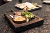 Fotografie gurmánské restaurace na dřevěný rustikální stůl
