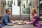 side view of beautiful adult couple having date at luxury restaurant
