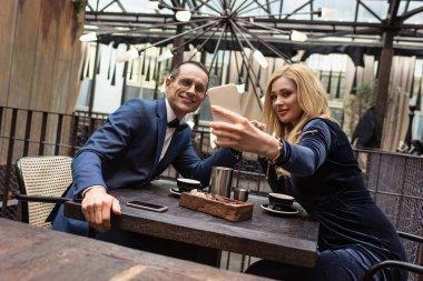 Beautiful adult couple taking selfie at restaurant stock vector
