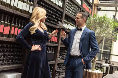 beautiful adult couple drinking wine in front of wine storage shelves