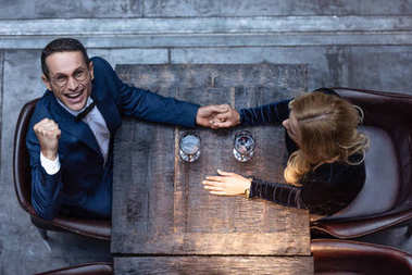 top view of beautiful adult couple holding hands at restaurant while drinking wine
