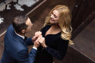high angle view of beautiful adult couple holding hands