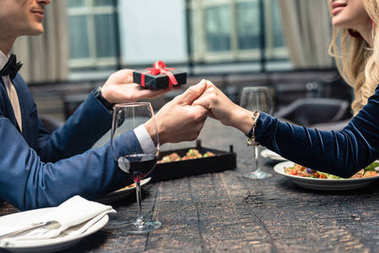 cropped shot of of man presenting valentines day gift to girlfriend at restaurant