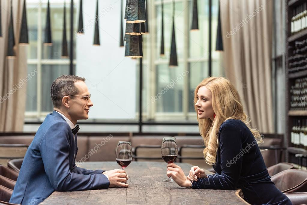 side view of beautiful adult couple drinking wine at restaurant