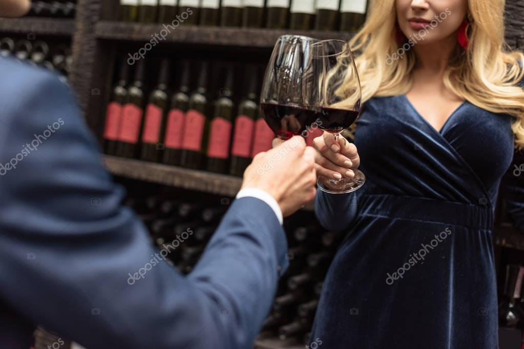 cropped shot of couple clinking glasses of wine