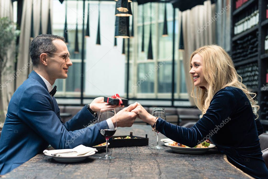 side view of man presenting valentines day gift to girlfriend at restaurant