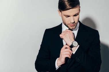 Thoughtful confident businessman in suit fixing his watch on white background