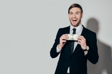 Excited businessman in suit showing dollar banknote on white background