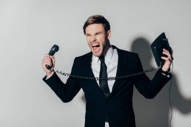 Angry businessman in suit screaming with phone in hands on white background